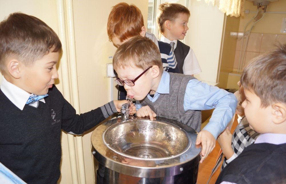 Дети пьют из питьевого фонтанчика в школе